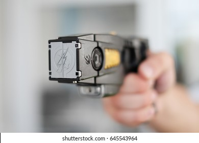 Closeup view of a loaded stun gun in a hand of a young man