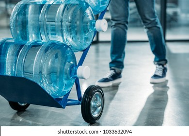 Close-up view of loader man pushing cart with water bottles