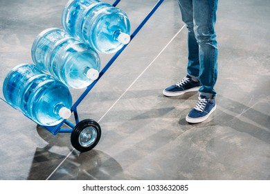 Close-up view of loader man standing by cart with water bottles