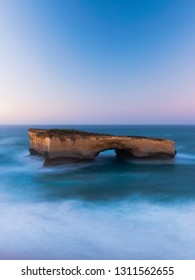 Close-up view of London Bridge arch rock formation with clear blue sunrise sky.