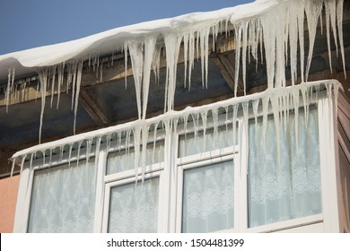 Closeup view of long sharp icicles hanging down from roof of house on sunny frosty cold winter day. Horizontal color photography.