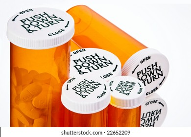 A closeup view looking down on the safety caps of five pill bottles of varying sizes.  One large bottle lies on it's side.  Large medication tablets are visible in the largest bottle.