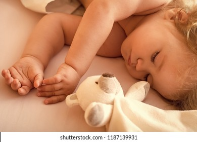 Closeup view of lovely small sleeping boy kid with blonde curly hair round cheeks and tiny fingers lying with closed eyes in bed with plush stuffed bear toy on white background, horizontal picture