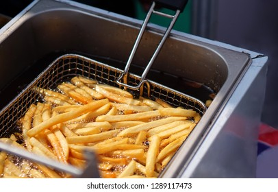 Closeup view of making french fries  deep frying in an equipment in fast or Indian fast food court