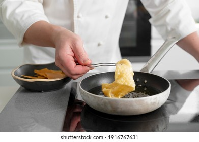 Close-up view of male chef cooking on frying pan. High quality photo