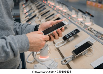 Closeup view of male customer hands, choosing white smartphone in the mobile phone store. difficult decision. Various choice