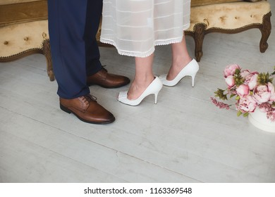 Closeup view of male and female legs isolated on white vintage wooden background in home interior. Happy moments of bride and groom on wedding day. Horizontal color photo.
