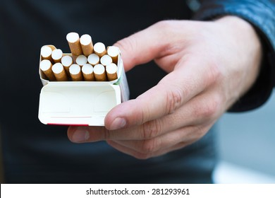 Close-up view of male hand take a pack of cigarettes