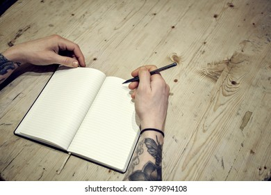 Close-up view of male hands with note book and coffee top view