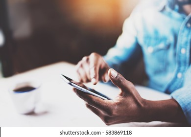 Closeup view of male hands touching mobile phone.African man using smartphone while sitting at the wooden table his modern home.Selective focus on hand.Blurred background,flares