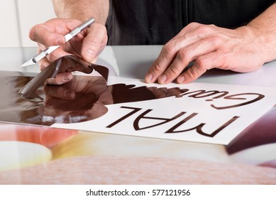 Close-up view of male master hands preparing adhesive shop window sign, using cutting tool on table surface