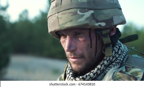 Close-up view of man with blood running on face wearing camouflage helmet and uniform looking around.