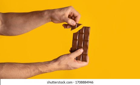 Closeup view of man breaking piece of chocolate from bar, orange background. Copy space. Panorama