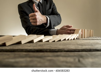 Close-up view of man in business clothes stopping dominoes row from crumbling and showing thumbs up gesture, on rough wooden table with copy space.
