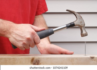 Closeup view of man hammering nail with house siding in background.