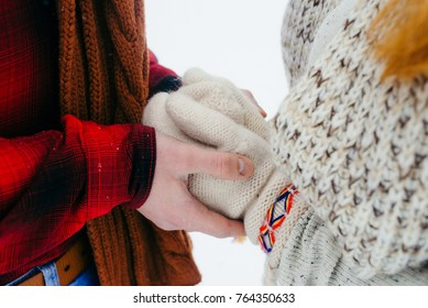 Close-up view of the man hands holding the woman hands in knitted gloves. Winter time.