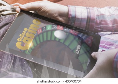 close-up view of man holding a tablet showing online casino profile. All screen graphics are made up.