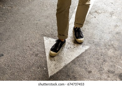 Close-up view of man legs in Brown Trousers and white shoes, lifestyle men fashion on street with white arrow symbol for concept ideas