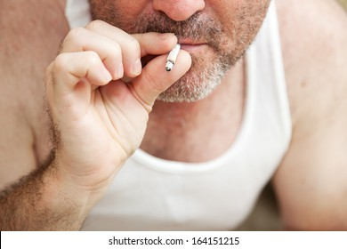 Closeup view of a man smoking a marijuana joint.  **Dramatization - no illegal narcotics were used in the making of this photograph**