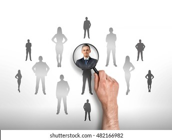 Close-up view of a man's hand focusing magnifier on a businessman who is surrounded by other people's sihlouettes. Employment issues. Looking for employees. Successful business staff.