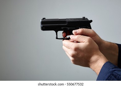 Closeup view of man's hands aiming with gun.