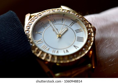 Closeup view of a man's wristwatch of luxurious taste and style of gold and diamonds.