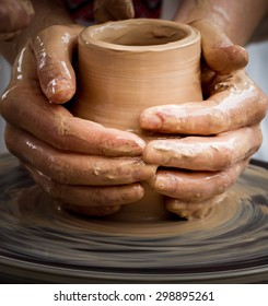 Close-up view of master working on pottery wheel and making clay pot