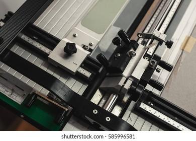 Closeup view of mat board cutting machine.