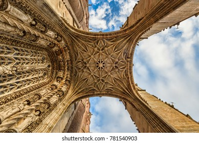 Closeup view of a medieval cathedral's entrance from ground up  under blue skies with fluffy white clouds
