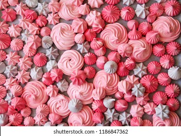 Closeup view of Meringues kisses in various star shapes in pink, light pink  and violet  colors. Homemade meringue cookies. Background .