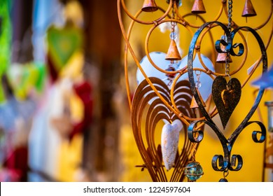 Closeup view of metal jewerly hearts with bells on the blurred background