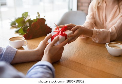 Closeup view of millennial guy giving his girlfriend Valentine's or birthday gift at table in cozy cafe. Unrecognizable young couple celebrating special occasion together, exchanging presents