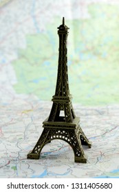 Closeup view of a miniature Eiffel Tower ontop of a map for travel concepts.