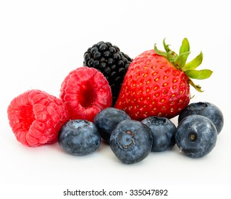 Close-up view of mixed, assorted berries blackberry, strawberry, blueberry, raspberry with green leave isolated on white background. Colorful and healthy concept. Black, blue, red, green