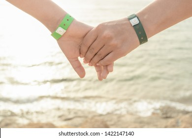 Closeup view of mother and son holding hands isolated at blue sea water background. People wearing green entrance wristbands of hotel resort or entertainment park. Happy summer holidays and vacations.