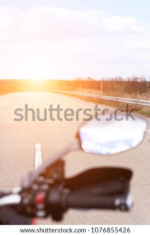 Close-up view of motorcycle handle bar with switches and mirroron an empty road in the background on a sunny day.