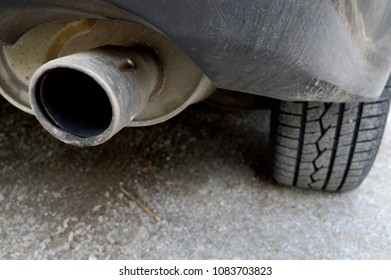 Closeup view of a muffler attached to a vehicle.
