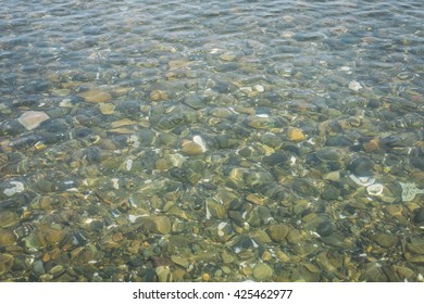 Close-up view of multicolored pebble of sea beach under clear water. Pattern of sea stone texture under water. Sea bottom with pebbles through clear water. Natural background.