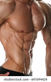 Close-up view of muscular male body in front of white background. Studio shot