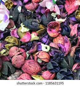 A close-up view of natural dried plants, barks, leaves, flowers, branches in a bowl of scented potpourri