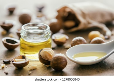 Closeup view of natural macadamia oil and Macadamia nuts on wooden board
