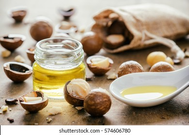 Closeup view of natural macadamia oil and Macadamia nuts on wooden board. Healthy product