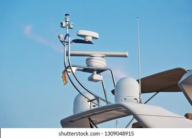 Closeup view of navigation radar system antennas yacht on blue sky background