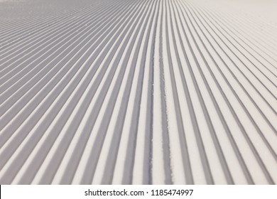 Close-up view of new groomed snow on empty ski slope