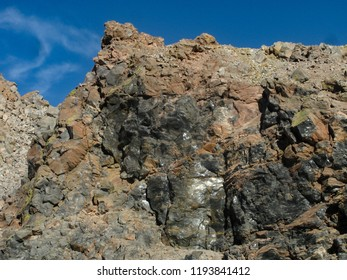 Closeup view of Obsidian Dome cliff, showing the shiny, black volcanic glass rock in its surface reflecting the sun, Sierra Nevada mountains, California USA.