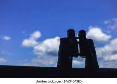 Closeup view of old black vintage silhouette of binoculars isolated at blue sky background. Horizontal color photography.