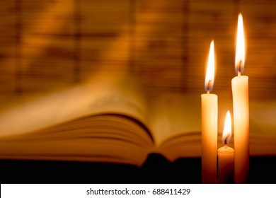 Close-up view of old burning candle with blurred old book on wooden background.  Education concept and Selective focus on tha candle with soft  light effect.