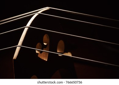 Closeup view of an old dusty cello, accentuated shapes with light.