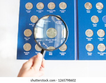 Close-up view of ollection of Quarter dollars (25 cents) coins in album - numismatic collection through a magnifying glass holding in hand - Rhode Island