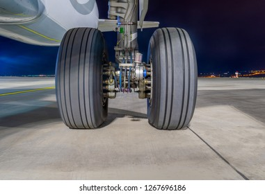 Close-up view on Airbus A320-232 aircraft's left main landing gear at night. Tbilisi International Airport, Tbilisi, Georgia